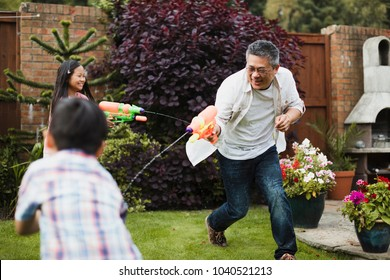 Family are having a water fight together with water pistols in the garden. The little girl is aiming for her dad, who is aiming for the little boy.