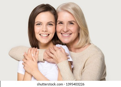 Family head shot studio portrait attractive grandmother embraces granddaughter smile looks at camera show love care, different ages generations females daughter and mother isolated on grey background