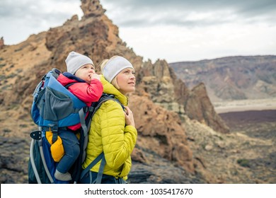 Family hike baby boy travelling in mother's backpack. Hiking adventure with child on autumn family trip in mountains. Vacations journey with infant carried on back, weekend travel in Tenerife, Spain.