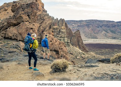 Family hiking with baby boy travelling in backpack. Hiking adventure with child on autumn family trip in mountains. Vacations journey with infant carried on back, weekend travel in Tenerife, Spain.
