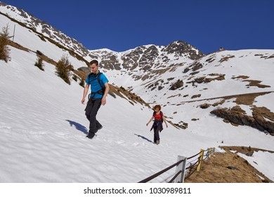 Family hiking into the rocky mountains at springtime