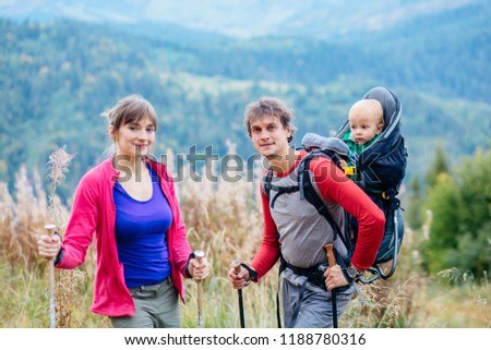 84c6cd1dbf Family hiking in the mountains. Father hiking with toddler in backpack.  Young mother