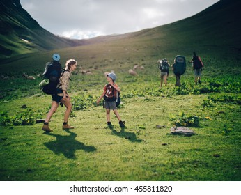 Family hiking in the mountains. A young happy mother and her son take a hike together in the mountains on a beautiful summer evening. Smile and enjoying their time together