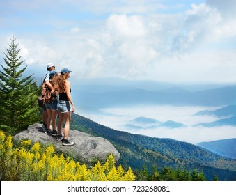 Family hiking on vacation. Father standing with arms around his family on top of mountain, over clouds, looking at beautiful foggy landscape.Near Asheville, Blue Ridge Mountains, North Carolina, USA.