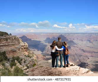 Family hiking on vacation, standing with arms around on top of the mountain, looking at beautiful summer mountains landscape. Blue sky in the background. Grand Canyon National Park, Arizona, USA.
