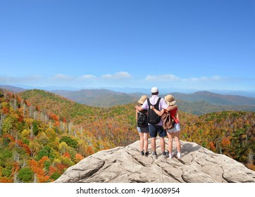 Family hiking on vacation, standing with arms around on top of the mountain, looking at beautiful fall mountains landscape foliage. Blue Ridge Mountains. Copy space. North Carolina, USA.