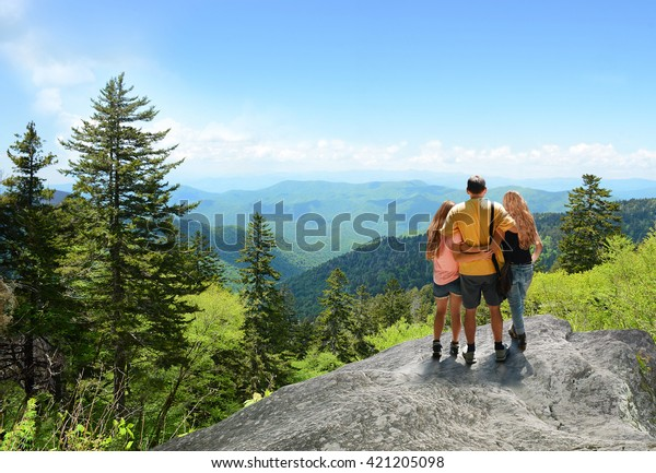 Family hiking on vacation, standing with arms around on top of the mountain, looking at beautiful summer mountains landscape. People enjoying beautiful view. North Carolina, USA.