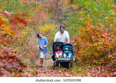 Family hiking with stroller in autumn park. Active father, baby and toddler in twin double pushchair. Fit healthy dad walking with jogger pram and kids. Outdoor activity in fall with young children.