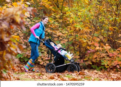 Family hiking with stroller in autumn park. Active mother, baby and toddler in twin double pushchair. Fit healthy mom walking with jogger pram and kids. Outdoor activity in fall with young children.