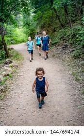 Family hiking together along a scenic mountain trail on a summer day. Selective focus Lifestyle photo of people outdoors enjoying nature and being active