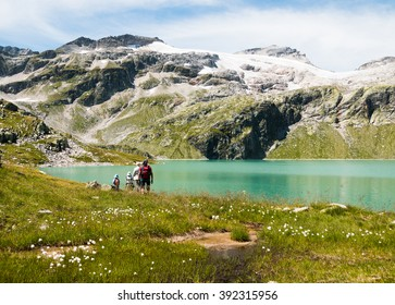 family hiking together around the glacier lake in the mountains with peaks view in alps near kaprun