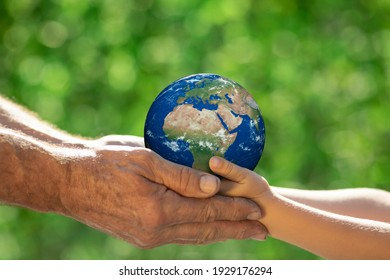 Family holding 3D planet in hands against green blurred background. Earth day spring holiday concept. Elements of this image furnished by NASA