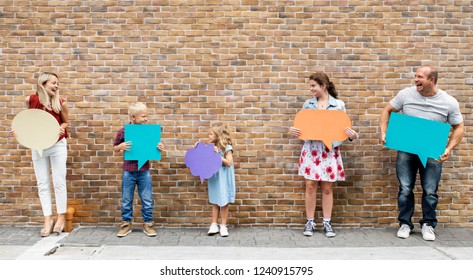 Family holding blank colorful speech bubbles by a brick wall