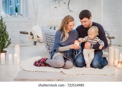 Family holding candle fire together in the hands, while sitting on the floor at home before Christmas and New Year.
