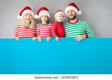 Family holding cardboard banner blank. Happy people playing at home. Christmas holiday concept. Copy space.