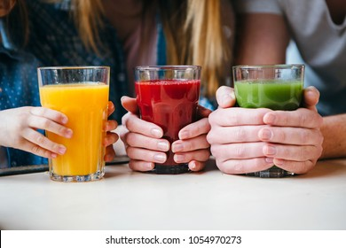 Family holding a glass of juice in hands.