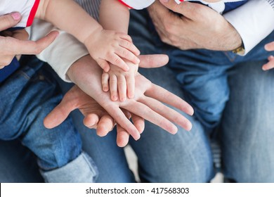 Family holding hands together closeup. Happy family