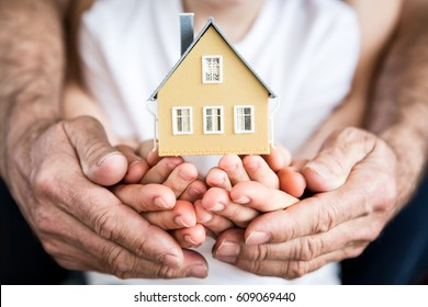 Family holding house in hands. Moving home and real estate concept