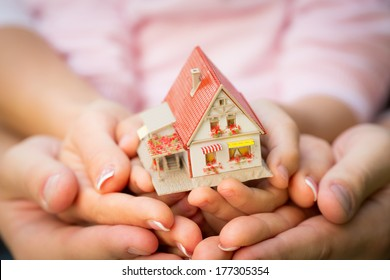 Family holding house in hands. Real estate concept