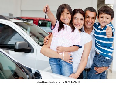 Family holding keys to their new car at the dealer