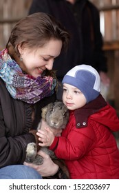 Family is holding rabbit on a farm