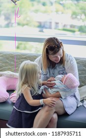 family holding and visiting newborn baby in hospital