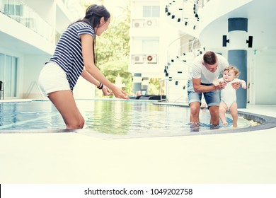 Family holiday. Father, mother and little daughter playing together at swimming pool.