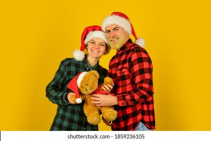 Family holiday. Loving couple yellow background. Christmas time. We love christmas. Couple in love with teddy bear soft toy enjoy christmas holiday. Family santa hats. Entertainment ideas for adults.