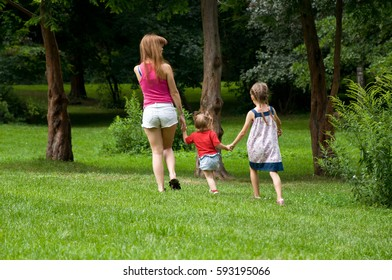 Family holiday in nature. Mother and two daughters have a walk in the park