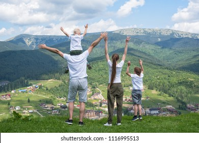 Family holiday. Parents and children stand with their hands up. Mountains on the background. Back view.