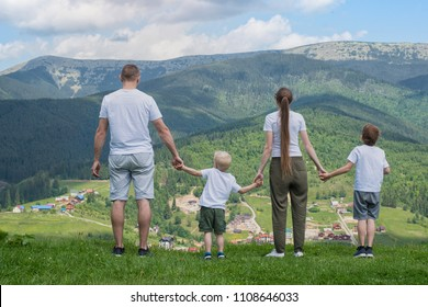 Family holiday. Parents and two sons admire views of the valley. Mountains in the distance. Back view