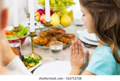 family, holiday, religion, thanksgiving, tradition and people concept - close up of girl praying at dinner at home