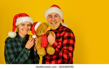 Family holiday. We love christmas. Loving couple yellow background. Christmas time. Couple in love with teddy bear soft toy enjoy christmas holiday. Family santa hats. Entertainment ideas for adults.