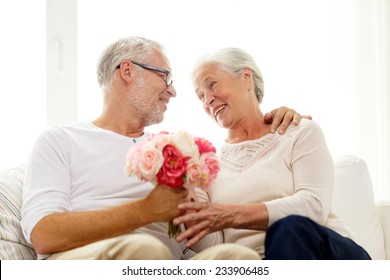 family, holidays, age and people concept - happy senior couple with bunch of flowers at home