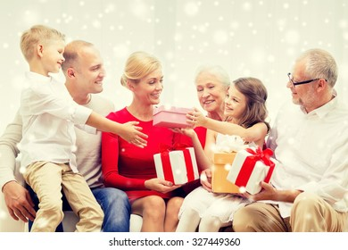 family, holidays, generation, christmas and people concept - smiling family giving each other presents  at home