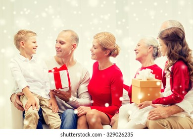 family, holidays, generation, christmas and people concept - smiling family with gift boxes sitting on couch and talking at home