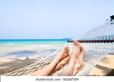 family holidays on the beach, feet of couple in hammock, relaxation concept background
