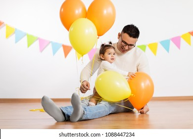 family, holidays and people concept - happy father and little daughter playing with helium balloons on birthday party