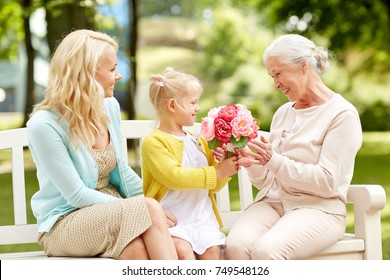 family, holidays and people concept - happy smiling granddaughter giving flowers to her grandmother sitting on park bench
