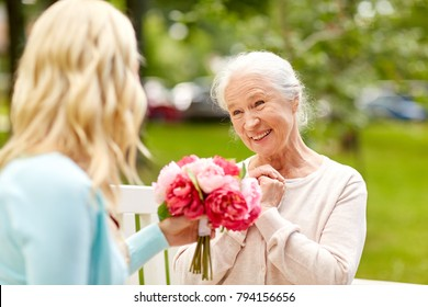 family, holidays and people concept - happy smiling young daughter giving flowers to her senior mother sitting on park bench