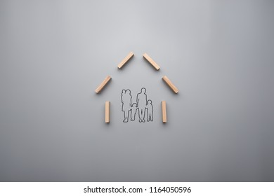 Family home concept with outline of a young family with children inside the frame of a house.