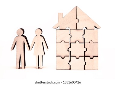 Family home concept. Wooden figures of man and woman in front of house on white background. figures of couple.