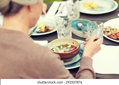 family, home, dinner, holidays and people concept - close up of woman eating soup in summer garden