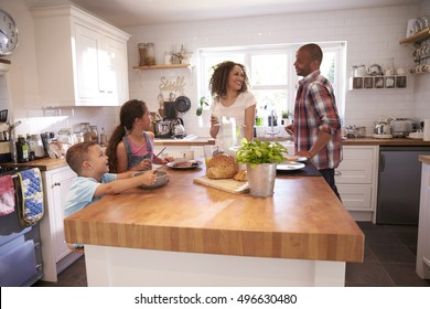 Family At Home Eating Breakfast In Kitchen Together