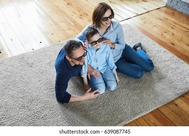 Family at home on a wooden floor watching TV in 3d glasses