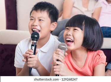 Family at home. Portrait of a happy Asian children singing karaoke through microphone in the living room