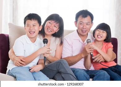 Family at home. Portrait of a happy Asian family singing karaoke through microphone in the living room