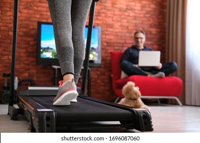 Family at home at quarantine isolation period during coronavirus pandemic. The man is working remotely. Woman exercising on a treadmill at home. Healthy lifestyle.