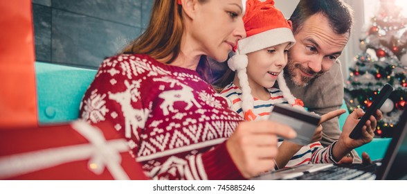 Family at home sitting on the blue sofa and shopping online during christmas