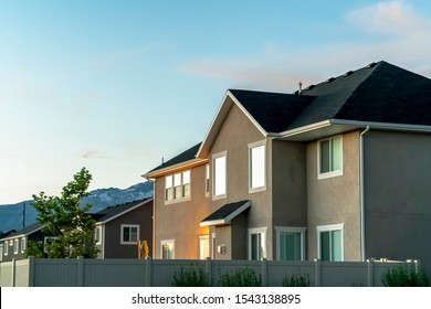 Family home surrounded by a white fence with mountain and sky in the background